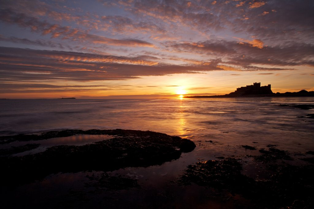 Mike Caine - Stocklandscapes - Stock Photography Bamburgh Castle, Northumberland; sunrise. Wide across sea and rocks
